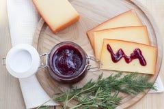 Отрезанный соус сыра и вишни на деревянной доске с укропом и розмариновым маслом Стоковое Изображение