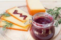 Отрезанный соус сыра и вишни на деревянной доске с укропом и розмариновым маслом Стоковое Фото
