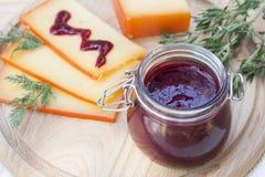 Отрезанный соус сыра и вишни на деревянной доске с укропом и розмариновым маслом Стоковые Изображения