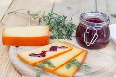 Отрезанный соус сыра и вишни на деревянной доске с укропом и розмариновым маслом Стоковые Изображения RF