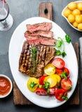 Отрезанный стейк говядины средства редкий зажаренный служил на белой плите с салатом томата и шариками картошек Барбекю, мясо bbq стоковое фото