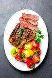 Отрезанный стейк говядины средства редкий зажаренный служил на белой плите с салатом томата и шариками картошек Барбекю, мясо bbq стоковые фотографии rf