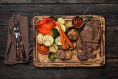 Отрезанный стейк с зажаренными овощами на деревянном столе Стоковая Фотография