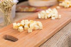 Отрезанный сыр на деревянной доске в кухне стоковое изображение rf