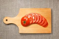 Отрезанный томат на деревянной разделочной доске с sacking Стоковое Изображение