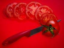 Отрезанный томат на красной предпосылке стоковые фотографии rf