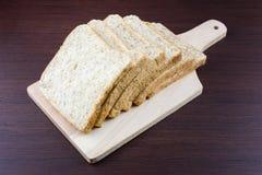 Отрезанный хлеб всей пшеницы на прерывать древесину Стоковые Фото