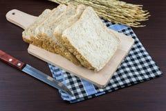 Отрезанный хлеб всей пшеницы на прерывать backgro древесины и скатерти Стоковое Изображение RF