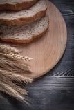 Отрезанный хлеб на деревянном пуке прерывая доски ушей ve рож пшеницы Стоковое Изображение RF