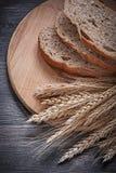 Отрезанный хлеб на деревянном пуке прерывая доски di ушей рож пшеницы Стоковые Фото