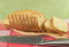 Отрезанный хлеб пшеницы на крупном плане разделочной доски Нож, красная салфетка Стоковые Изображения