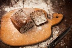 Отрезанный хлеб рож на крупном плане разделочной доски на таблице Стоковое Изображение RF