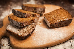 Отрезанный хлеб рож на крупном плане разделочной доски на таблице Стоковое Изображение