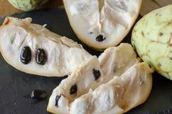 Отрезанный cherimoya на черном каменном столе конец вверх Взгляд сверху угла стоковое фото rf