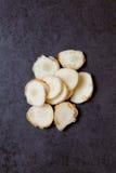 Отрезанный galangal на таблице Стоковая Фотография