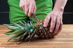 Отрезать ананас на разделочной доске дуба стоковое фото