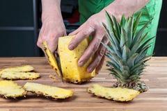 Отрезать ананас на разделочной доске дуба стоковое изображение