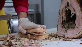 Отрезать мясо свинины для того чтобы подготовить сандвич в стойле еды Стоковые Изображения RF