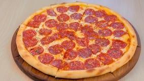 Отрезать пиццу салями на деревянной доске на таблице Взгляд со стороны конца-вверх сток-видео