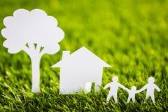 Отрезок бумаги семьи с домом и дерева на траве Стоковое Изображение RF