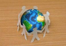 Отрезок бумаги людей стоя в круге вокруг глобуса Стоковое Фото