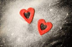 Отрезок из теста на floured таблице, черная таблица 2 красный сердец, космос для текста Взгляд сверху Стоковая Фотография RF