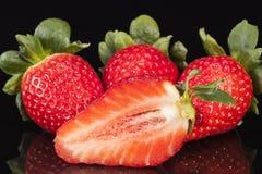 Отрезок и все свежие фрукты красной клубники изолированные на черной предпосылке Стоковые Изображения