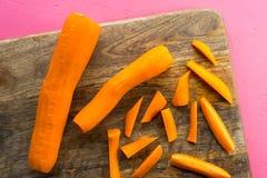 Отрезок морковей в прокладки и все морковей на разделочной доске Стоковое фото RF