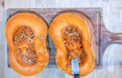 Отрезок тыквы в 2 половины на деревянной разделочной доске на деревянном столе стоковая фотография rf