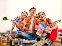 Отремонтируйте дом здания группы людей используя инструменты ролика краски Стоковые Фотографии RF