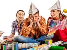 Отремонтируйте дом здания группы людей используя инструменты ролика краски Стоковое фото RF