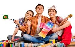 Отремонтируйте дом здания группы людей используя инструменты ролика краски Стоковые Фото