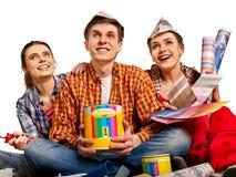 Отремонтируйте дом здания группы людей используя инструменты ролика краски Стоковое Фото