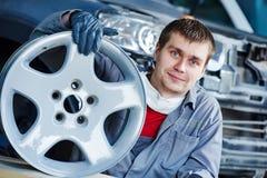 Отремонтируйте работника механика с оправой диска колеса автомобиля светлого сплава Стоковые Изображения