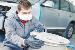 Отремонтируйте работника механика с оправой диска колеса автомобиля светлого сплава Стоковые Изображения RF