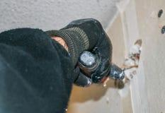 Отремонтируйте работу в квартире Рука ` s работника покрывает отверстие в стене Стоковое Фото