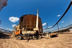 Отремонтируйте работу на замене более низких поясов старого ржавого танка для стоковые фото