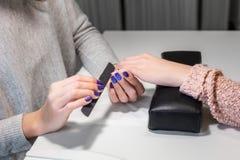Отростчатые ногти с пилочкой для ногтей наждака в салоне красоты Стоковые Изображения