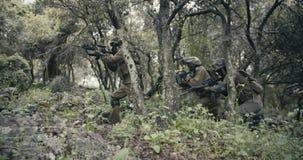 Отряд полностью вооруженных солдат командоса во время боя в пейзаже леса акции видеоматериалы