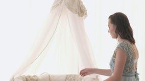 Отслеживать мать кладя младенца для того чтобы спать пока идущ Привлекательная женщина держа младенца в руках и прогулке через жи стоковое изображение rf