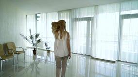 Отслеживать съемку белокурой женщины идя в лобби офисного здания в замедленном движении видеоматериал