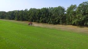 Отслеживать съемку красного катания трактора на крае зеленого поля с молодыми ростками акции видеоматериалы