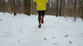 Отслеживать съемку мужских ног бегуна бежать на пути снега в лесе зимы видеоматериал