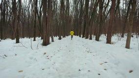 Отслеживать съемку мужского бегуна в желтом пальто в лесе зимы акции видеоматериалы