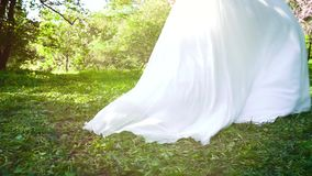 Отслеживать съемку невесты в длинном платье идя в зацветая сад в замедленном движении акции видеоматериалы