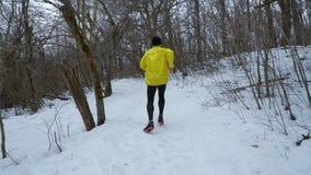 Отслеживать съемку спортсмена в желтом пальто бежать вверх холм в лесе зимы сток-видео