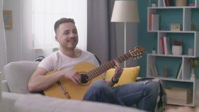 Отслеживать человека играет гитару для его друзей в уютной живущей комнате сток-видео