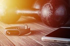 Отслежыватель, smartphone и гантели фитнеса на деревянной предпосылке Стоковая Фотография RF