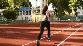 Отснятый видеоматериал замедленного движения женского бегуна начиная побежать на линии следа на малом стадионе outdoors Подходяща видеоматериал