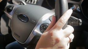 Отснятый видеоматериал замедленного движения крупного плана женских рук водителей на рулевом колесе автомобиля